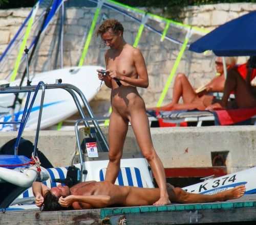 Couple is playing at the nude beach. They have great fun and love to be naked