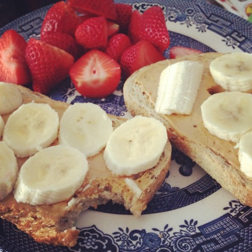 vegetarian-and-fit:  breakfast this morning! two pieces of multigrain bread with peanut butter and chopped banana, a handful of strawberries