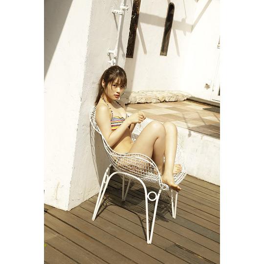 虹色のボーダーのビキニを着て椅子に座っている渋谷凪咲の画像