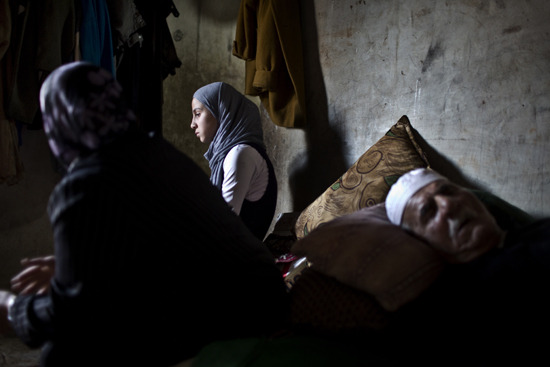 Photo: An elderly Syrian refugee suffering from Parkinson's disease sleeps in a room in a ramshackle home on a cattle ground in Tripoli, Lebanon, surrounded by his daughter-in-law and granddaughter....
