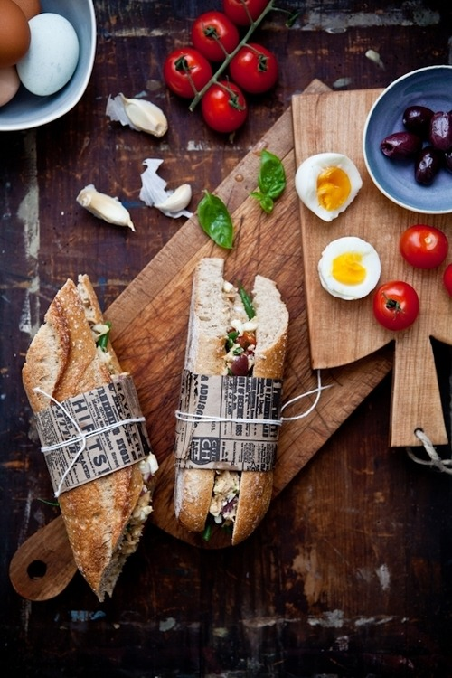 prettygirlfood:  Tuna Nicoise Sandwiches Makes 4 large sandwichesIngredients:1 cup French green beans4 large eggs2 cans tuna in oil, drained, coarsely flaked1 cup cherry tomatoes, quartered1/3 cup small black olives, pitted2 shallots, thinly sliced1/4 cup torn and loosely packed basil leaves (no need to chop fine, just use your fingers)3 tablespoons olive oil1 tablespoon red wine vinegarkosher salt and fresh ground pepper to taste2 anchovy fillets, finely crushed with back of fork1 garlic clove, minced1 baguette (regular or gluten free)Directions:Bring a large pot of water to a boil, add a pinch of salt and blanch the green beans in it for about 3 minutes. Drain them in a colander and place them in a bowl full of ice until they are completely cold. Drain again well and reserve. The goal is to cook the green beans just enough to remove the raw taste of their uncooked selves but still keep the vibrant color and nice crunch of their barely cooked selves.Bring another large pot of water to a boil. Add the eggs to the boiling water, cook for 6 minutes (soft yolks). Remove them from the water and run them under cold water until they are cooled enough to peel. Once peeled, coarsely chop them up and add them to the green beans. Add the tuna, tomatoes, olives, shallot and basil. Toss well to combine.In a small bowl, whisk the oil, vinegar, anchovy and garlic. Season to taste with salt and pepper and pour this vinaigrette over the green bean and eggs. Toss well until everything is nicely seasoned with the vinaigrette.Cut the baguette in half horizontally and spread the Salade Nicoise all along its bottom part. Wrap with a layer of parchment paper and then a layer of foil or plastic wrap. Refrigerate 6 hours or overnight. The next day, cut the baguette into 4 pieces and serve.