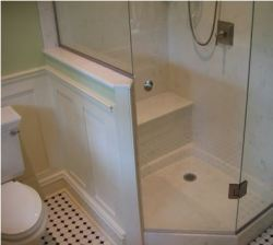 Bathroom with half-wall and wainscot on corner shower with bench.