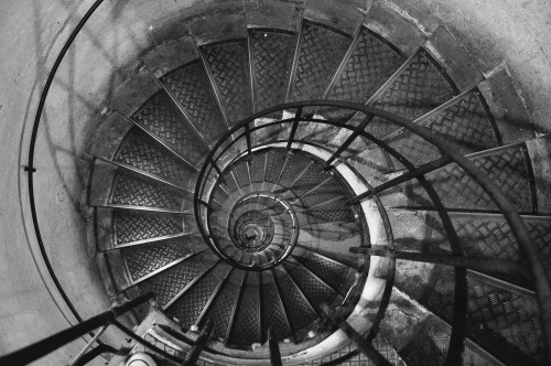 The spiral staircase descent inside the Arc de Triomphe, Paris.