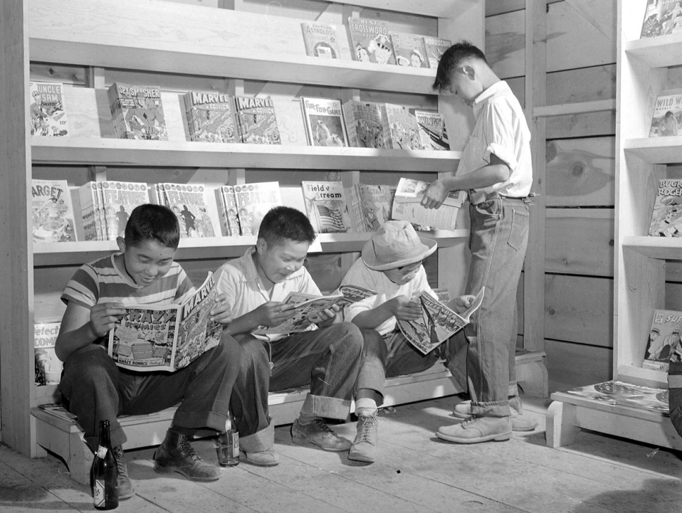 Four young evacuees from Sacramento, California read comic books at the newsstand in the Tule Lake Relocation Center. Newell, California, 1942.&