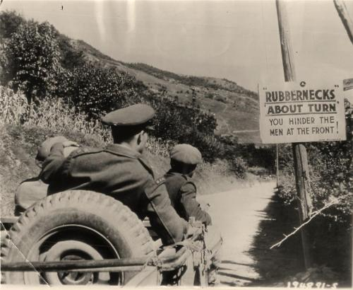 "WWII Soldiers Pass ""Unwelcome"" Sign Near Front Lines in Italy. These men in a jeep pause to study a sign meant for 'Unwelcome Visitors' which is posted a few miles before front lines in the Crespino area, Italy. A.P. wire photo from U.S. Signal Corps."