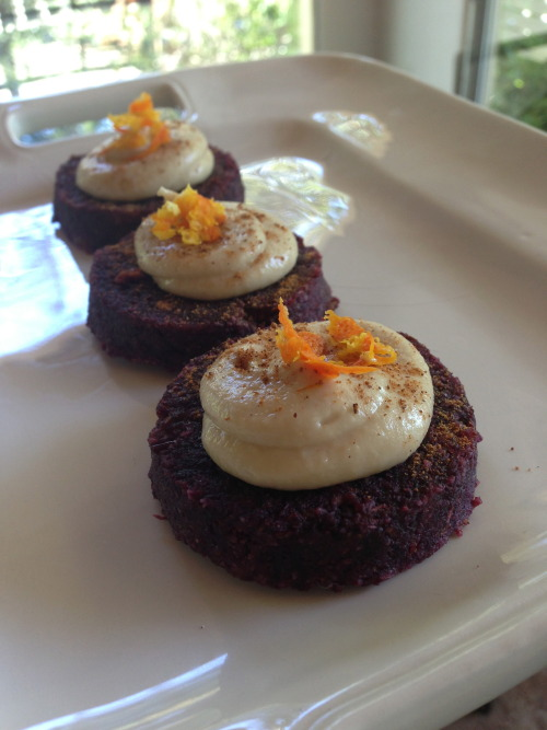 Raw Carrot Cake with Cashew Creme  This has recently become my favorite snack. So easy to make. It has a few simple steps and I have made it four times now, so I have it down. The original recipe is from Russell James, The Raw Chef. I watch his podcast and really enjoy his take on preparing raw dishes. You can subscribe to his free podcast on itunes here. Ingredients 3 cups carrot, grated. Above you see that the cakes look red - that's because I used heirloom red carrots, I love the color and it's unexpected, which I love as well. 2 cups almond meal 1/4 cup chopped raisins. I love the golden ones, though you can use whatever. It would be good with currants too I bet 1 teaspoon nutmeg (and a little for the garnish) 1 1/2 teaspoon pumpkin pie spice 1 cup date paste (To make the paste, blend 3/4 cup pitted dates with 1/2 cup of juice. I used tangelo this time, have used orange and tangerine in the past) - Put the dates and juice in the Vitamix and blend for 2 min until velvety smooth 1/2 teaspoon sea salt 1 T grated rind (of the orange or tangelo you used in the date paste) 1/2 cup dried coconut (raw) Blend all of the ingredients in a mixer, then form into small cakes. I use a ring mold about 3 inches in diameter. I have tried small, large, loaf - pick one try it and the next time try something else. Make sure that whatever form you pick, have each cake consistent in size to have even drying. Once you have formed the cakes (this recipe makes 20 the size you see above) - put them on a dehydrator sheet and dry at 105 for about 12 hours. This will give them a very nice skin on the outside and the inside will still be very moist. Take them out and let them cool on the counter. Cashew Creme Frosting This can go a lot of ways depending on how inventive you are, so feel free to play with it. The base recipe is: 1 1/2 cups soaked raw cashews, blended until velvety smooth 2 tablespoons raw honey 3 tablespoons Coconut Oil. I used Nutiva Coconut Manna as it has a nice thickness that works for the icing 1 teaspoon vanilla pinch sea salt Blend all of this in the Vitamix until so smooth you can't believe it's ground nuts. Then blend 30 seconds more. Place in a frosting bag and put in the fridge for 60 min to cool, this makes piping it onto the cakes a lot easier and it will be runny. Note: Russel says add 1/2 c water and I tried that and it was too runny. Once thickened you can frost the cake and garnish. I used nutmeg and grated tangelo. Cool and serve with iced Almond Milk. ps. Thanks to good friends George and Andrea who are looking at buying a home in Ojai in an orchard and brought us a bag of tangelos from the property, which I used in this recipe. Variations. You could add chopped raw pecans You could add cinnamon and cardamon You could use ordinary orange carrots ;-) You could add oat flour or cashew flour in place of some of the almond flour. The original recipe calls for pecan flour, which I don't have access to, now, if I lived in Texas… Let me know if you try this out, and write a comment to let me know how they came out.  Til we eat again…