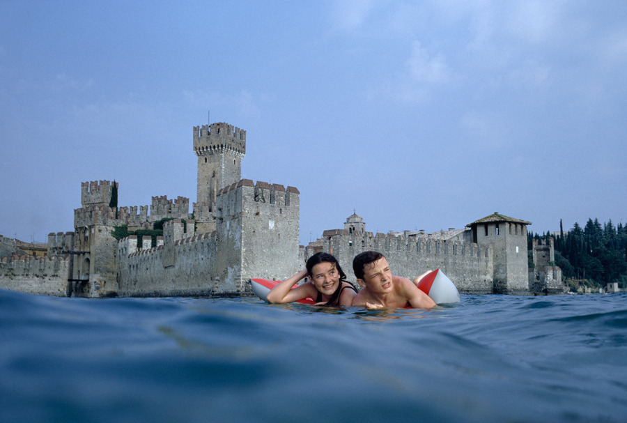 natgeofound:  Twins drift on raft in lake water in front of medieval castle in Sirmione, Italy, July 1968.Photograph by Joe Schershel, National Geographic