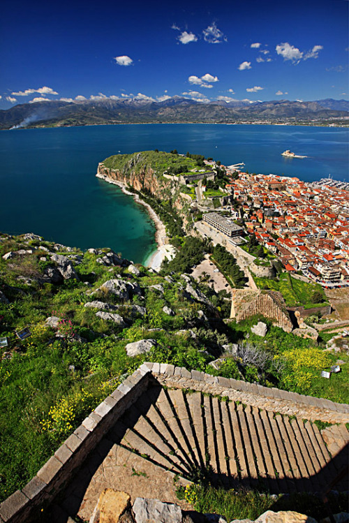 Nafplion the 1st capital of Modern Greece Nafplion, a seaport town, is one of the most charming towns in Greece.Stepped streets overhung with balconies dripping with bougainvillea, beautiful neoclassical buildings, enticing shops, restaurants and cafes shape the most part of the town. Two museums, two hilltop Venetian fortresses and… a miniature Venetian castle on an island in the harbour, called Bourtzi, which despite the fact that it was originally created as fortress it also served as a hotel from the 1930-1970, create a destination like no other. Nafplion brings you face to face with the beginnings of modern Greece. For several years after the Greek War of Independence (1821-28), Nafplion and not Athens as many may think, was the original capital of the First Hellenic Republic.