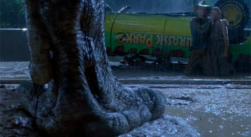 Looking at Dinosaurs: 'Jurassic Park' and Its Powerful Hold on a Generation Jurassic Park is Steven Spielberg at his best, a movie made by a man who understands and wields the all-encompassing power of cinema. So much of the story is about regular people—intelligent, and at the top of their game, but still fairly average people—being tossed into, essentially, a movie. The centerpiece of the film, still its very best scene, is when the Tyrannosaurus Rex breaks free from its enclosure and attacks Tim and Lex in their Ford Explorer after the cartoonish lawyer Donald Gennaro ran in fear to a nearby bathroom. (It's been said before, but man, Spielberg must've hated lawyers something terrible when making this movie.) What struck me this time is that, for a good chunk of the sequence, we are not the only ones watching the terror unfold. There's a voyeuristic streak laced with a chaser of control throughout—Hammond, Muldoon, and others watch and help navigate the failed tour—most disquieting as Grant and Malcolm sit in their Explorer, paralyzed and initially helpless, just watching. Jurassic Park is packed with scenes where someone is trying to gain or maintain control despite their physical separation from those they wish to dominate: Dennis Nedry wheedling his way onto a ship to the mainland, Hammond and Malcolm bickering over who can lead Ellie to a power grid quicker, that first tour around the park, and on and on. There are also a handful of scenes where these characters, so sure of their power, attempt to break the seal, to break the fourth wall, as when the scientists escape from the introductory video explaining how these dinosaurs were created to interact with those people working behind the glass. These are characters who want control, unable to contain their curiosity, thus creating chaos. CLICK HERE TO EXPAND THIS ARTICLE