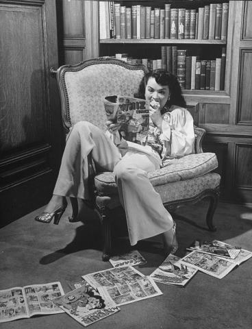 Actress Buff Cobb, reading comic books at home in 1946. Buff was married to television personality, Mike Wallace.