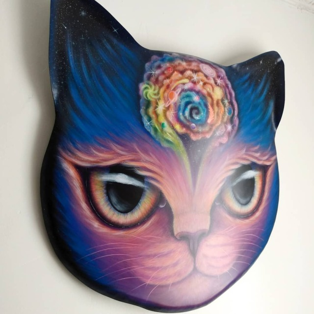 holding painting in my hands. metal had been cut out into a cat face shape curved toward the walls with ears curving forward. purple fur fades to dark blue, then into black starry sky on the ears.