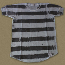 Tender's English made… hand-striped Tshirts are the result of an experiment to paint dye by hand directly onto a finished garment. Each one is individually painted and is unique. This Tshirt has been painted in black and purple stripes with logwood. The Tshirt itself is made out of cotton interlock (thicker and more robust than single jersey), cut in one piece with no shoulder seam. This follows research into early Twentieth Century underwear and sportswear. By cutting in one piece there is no shoulder seam to rub against the skin, or stretch or fray. Also, as the folded shoulder line is horizontal, this cut gives slightly more room for the arm to move than a standard slope-shouldered cut. To achieve a folded shoulder, the tube of fabric which is originally knitted first needs to be cut and spread out flat (as opposed to tubular Ts, a vintage staple). An advantage of cutting flat rather than tubular is that shape can be put in at the armpit, reducing the tension on the fabric under the arms, which can tear on tubular-cut Ts. Trestleshop (UK)