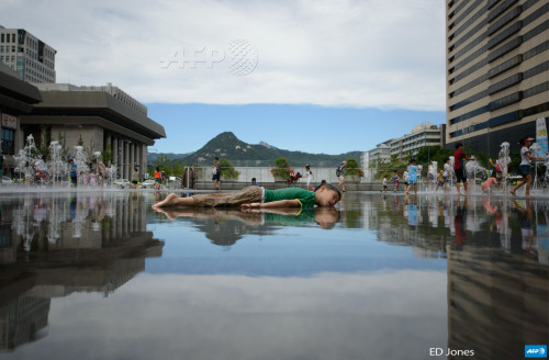 afp-photo:  REPUBLIC OF KOREA, SEOUL : A child lies in a pool of water to cool down in central Seoul on August 1, 2014. South Korea's state weather agency issued a heat wave warning for Seoul for the first time this year, advising people to stay indoors. Heat wave warnings are issued when the daytime high is expected to stay above 35 C (95F) for two or more consecutive days, according to state media. AFP PHOTO / Ed Jones