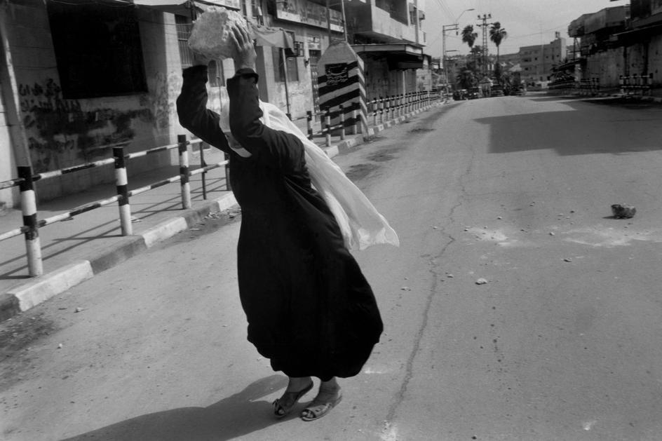Palestine Square, Gaza City, Gaza. 1993. Intifada. Palestinian woman breaking stone into fragments to throw at soldiers down the street after Friday prayer. © Larry Towell/Magnum Photos