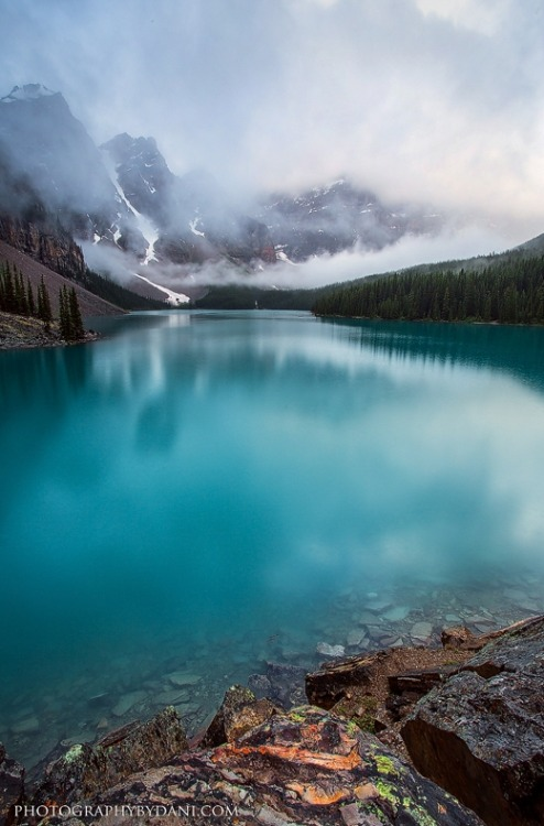 earth-song:  Moraine Lake Banff National ParkThe beautifully moody summer rain clouds hover over one of Banff National Park's true gems. The rain and clouds made for some great contrast to reveal the colourful lichen on the rocks. by Dani-Lefrancois