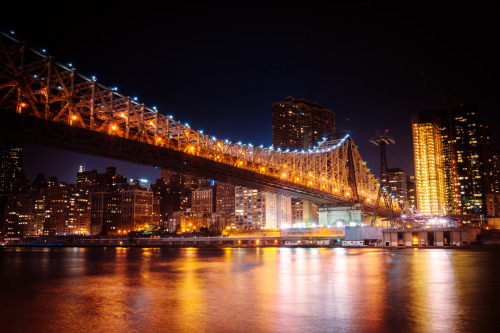 "Ed Koch Queensboro Bridge and the New York City skyline at night. Roosevelt Island view.—-   When the night falls hard onto the city's shoulders and the sky drapes a dark blanket over the skyscrapers and buildings, it's hard to contain the effervescent charm that bursts forth after the sun has retreated.    —-  This is the Queensboro Bridge which is known by a few other names depending on where you are from and how long you have lived in New York City. Despite growing up in Queens, I will always think of this bridge as the 59th Street Bridge because I think I belonged to one of the few families in Queens that for whatever reason associated the bridge more with 59th Street in Manhattan. It's also known as Queens Bridge which is a shortened form of Queensboro Bridge. Its current official name is the Ed Koch Queensboro Bridge, named after the now deceased former mayor of New York City who held office from the late 70s to the early 80s. He was definitely a ""character"" (as we say :) ).    The vantage point is from Roosevelt Island and this is the result of a 30 second exposure taken with the Sony A99. It was taken on a bitterly cold night in the beginning of March while I was having a spirited conversation with one of the Roosevelt Island security guards regarding the abandoned smallpox hospital further down the island. I tend to love to shoot long exposures alone but it was great to have the company (and quirky conversation) that night. It's those type of moments that make me love the city: little bursts of spontaneity and brevity while watching the lights sparkle in the city's eyes.  —-View this photo with a comment thread on my Google Plus page—-View ""New York Night - Queensboro Bridge and the Manhattan Skyline"" in my photography portfolio here, email me, or ask for help."