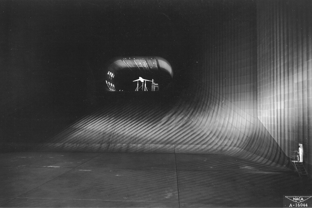 "Behold, the world's largest wind tunnel!  (1947) Looking down the throat of the world's largest tunnel. The scene is NACA's 40 x 80 foot wind tunnel at Ames Aeronautical Laboratory, Moffett Field, California. The camera is stationed in the tunnel's largest section, 173 feet wide by 132 feet high. Here at top speed the air, driven by six 40 foot fans, is moving about 35 to 40 miles per hour. The rapid contraction of the throat (or nozzle) speeds up this air flow to more than 250 miles per hour in the oval test section, which is 80 feet wide and 40 feet high. The tunnel encloses 900 tons of air, 40 tons of which rush through the throat per second at maxium speed. Dwarfed by the immensity of the tunnel structure, the experimental model seen here is actually almost 50 feet long. Embodying a sharply swept-back wing suitable for supersonic flight, it is undergoing tests designed to improve the landing characteristics of this type of airfoil. Mounted on struts connected to scales under the test section, it is ""flown standing still"" while each element such as lift and drag is measured and air pressures occuring across the wing are recorded. Information gathered from such tests were made available to the nation's aircraft manufacturers by the NACA (now NASA), an independent agency of the U.S. Government."