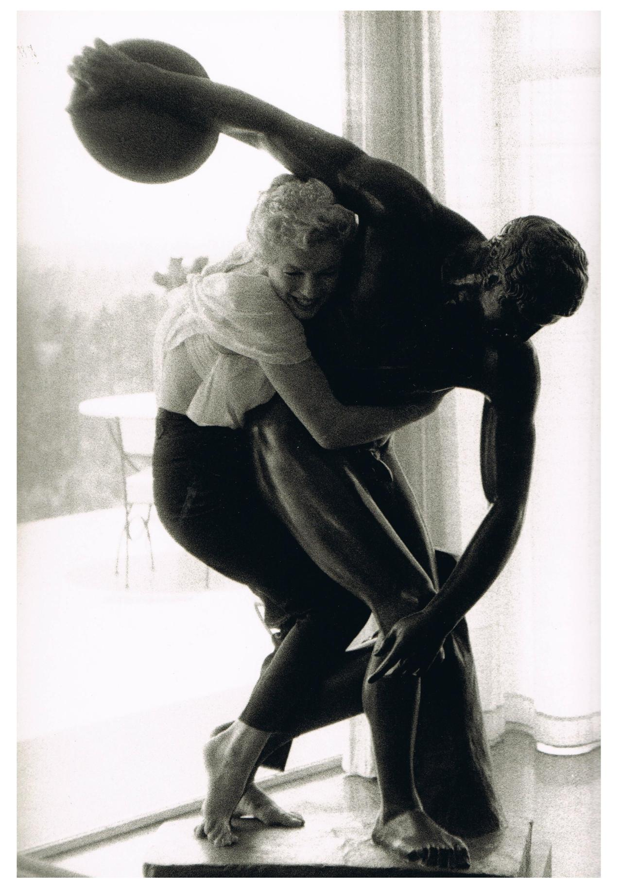 Marilyn Monroe posing with hairdresser Sidney Guilaroff's statue of the discus thrower. Photograph by Milton Greene.