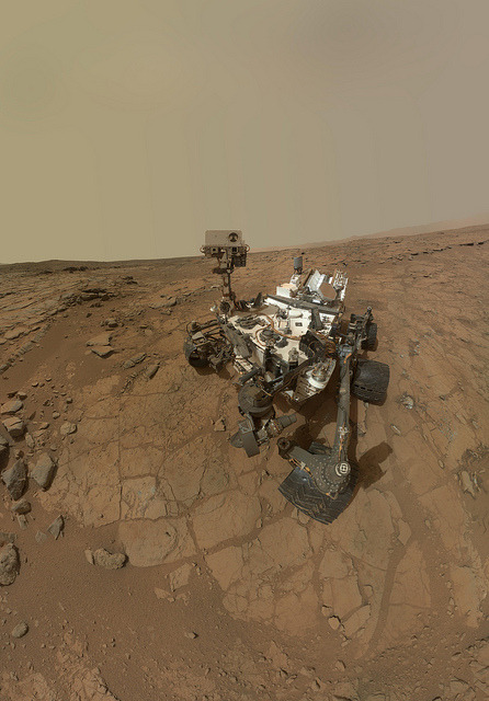 "Curiosity Rover's Self Portrait at 'John Klein' Drilling Site by NASA Goddard Photo and Video on Flickr.   This rectangular version of a self-portrait of NASA's Mars rover Curiosity combines dozens of exposures taken by the rover's Mars Hand Lens Imager (MAHLI) during the 177th Martian day, or sol, of Curiosity's work on Mars (Feb. 3, 2013). The rover is positioned at a patch of flat outcrop called ""John Klein,"" which was selected as the site for the first rock-drilling activities by Curiosity. The self-portrait was acquired to document the drilling site. The rover's robotic arm is not visible in the mosaic. MAHLI, which took the component images for this mosaic, is mounted on a turret at the end of the arm. Wrist motions and turret rotations on the arm allowed MAHLI to acquire the mosaic's component images. The arm was positioned out of the shot in the images or portions of images used in the mosaic.  Hi, Curiosity!"