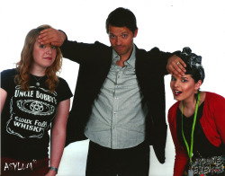 "wurmstache:  Ellen and I in our other photo op - I asked Misha if we could have a 'sort of double smiting situation' and the little shit looked me in the eyes and said ""huh, I've never smited two girls at the same time before"".  Guh.  He'd already half pulled us into a hug by this point, so as we tried to explain what we wanted, he was rubbing our backs - this made it VERY DIFFICULT to think straight XD. We were going for scared face, but Ellen ended up excited and I ended up predictably derping. Still, Misha looks perfect (obviously) and the pic makes me laugh every time I see it, so that's all good :)."