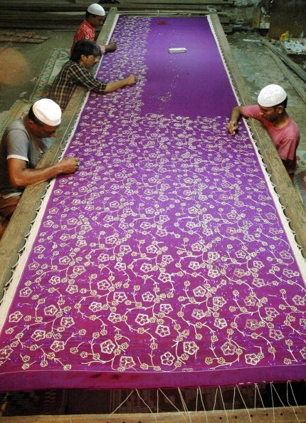Indian Muslim artisans work on a hand embroidered silk saree (traditional Indian women's outfit) at a workshop in Hyderabad, southern India,