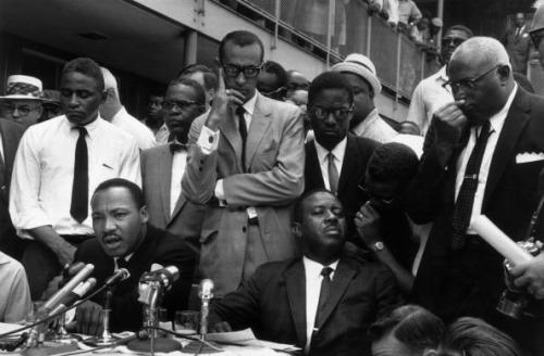 "pbsthisdayinhistory:  May 10, 1963: Birmingham Campaign Ends in Victory On this day in 1963, the Birmingham Campaign ended with a victory. Martin Luther King, Jr. and Fred Shuttlesworth signed a truce agreement with local officials to outline a 'limited desegregation plan,' which promised to: Remove ""White Only"" and ""Black Only"" signs from restrooms and drinking fountains in downtown Birmingham Desegregate lunch counters Deploy a ""Negro job improvement plan"" Release jailed demonstrators Create a biracial committee to monitor the agreement Desegregation, however, would take place slowly over the next few months. Learn more about the Birmingham Campaign with PBS Black Culture Connection. Photo: Martin Luther King Jr. gives a press conference regarding an agreement reached on a 'limited desegregation plan' outside the Gaston Motel in Birmingham, Alabama (Photo by Ernst Haas/Ernst Haas/Getty Images)"