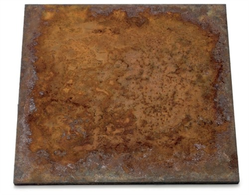 "Sink by William Anastasi, 1970 rusted steel, 20"" x 20"" ""I was chatting with a scientist I'd just met at a party, and our conversation turned to the why and how of rust.  I was told that iron ore from the mountain is all but useless, except maybe as a doorstop.  It's not malleable.  But some forgotten discoverer learned that when heated to a sufficient intensity it liquified.  Then if the surface was skimmed off, the remainder, when cooled off and solid again, behaved diffferently from the ore of its earlier state.  It would now be wonderfullly malleable—we call it steel.  But a marvelous thing about steel is that wherever it is, it wants to take from the moisture in the atmospher neither more nor less than the very elements that had been ealier skimmed away.  The result of this struggle brings about the kind of corrosion we call rust.  I thought it's as though the steel has a memory and wants to go home.  I said, ""This is the most poetic thing I've ever heard of.""  The next day I drove to a steel supplier in Brooklyn and brought back two plates of hot-rolled carbon steel.  I leaned one against a wall and lay the other flat on the floor.  I poured on it a couple of ounce s of tap water and watched.  The dark blue surface begain to blister with the familiar off-red before my eyes.  Within a few days I wrote a recipe so that anyone could repeat the operation:  Set a rectangular piece of hot-rolled carbon steel level on a floor.  Pour on it a measure of tap water so that the resulting pond holds its position short of overflow.  Each time the water evaporates, repeat.  I titled it Sink, for the verb, since the surface would be eaten away over the years."" -William Anastasi from an interview he conducted with himself for Art on Paper magazine, May 10, 2007."