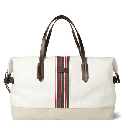 GUCCI Getaway: The Gucci Striped Cotton Canvas Holdall features a brisk design with trademark green and white center stripes, white and beige cotton canvas and leather accents for a light and functional weekend man bag. $790.