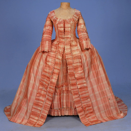 PLAID SILK ROBE a la FRANCAISE, c. 1765. Red, pink and cream taffeta open gown with 3/4 sleeve and U-neck trimmed in self furbelows, back having two double box pleats falling from the neckline flanked by inverted pleats at the waistline. Trained skirt with deep satin hem facing on train, bodice lined in linen, matching petticoat having three front furbelows, upper back panel of linen with waist tie.