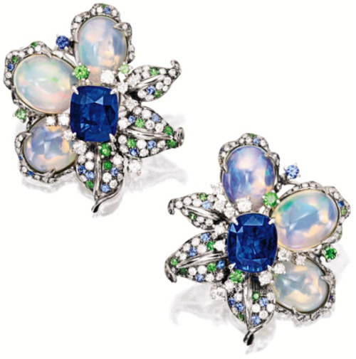 diamondsinthelibrary:  Sapphire, opal, and diamond earrings. Of floral design, each flower head centring on a cushion-shaped sapphire altogether weighing approximately 10.00 carats, highlighted by three jelly opal petals altogether weighing approximately 17.20 carats, embellished by leaves set with circular-cut diamonds, sapphires and tsavorite garnets, mounted in 18 karat blackened and white gold. Via Sotheby's.