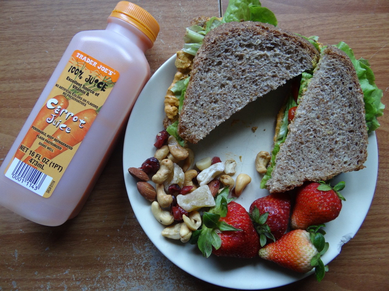 mayur-asana:  today's lunch: ezekiel bread sandwich with red pepper hummus, mustard, local lettuce, and tomatos ; strawberries ; cashew almond cranberry pineapple trail mix ; carrot juice