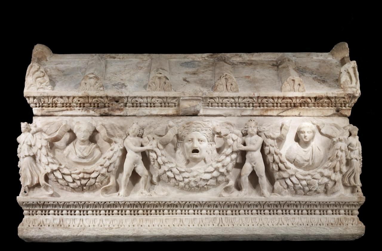 Ancient Roman Garland Sarcophagus, made of Dokimeion marble, and dates to between 150 and 180 (Imperial). Courtesy & currently located at the Walters Art Museum, Baltimore, USA:  Unlike many sarcophagi, this one is carved on all four sides in high relief. Garlands held by winged goddesses or personifications on the corners and Eros (Cupid) figures on the sides support the busts of a crowned deity (left) and a young girl (right). The sarcophagus was probably intended for her. In the center, on both the front and back, is a theatrical mask-on this side Tragedy, on the other, Comedy. Medusa heads decorate the ends. The lid takes the form of a temple roof with a pediment (triangular gable) at each end. This sarcophagus can be traced to a particular workshop active near the ancient quarry of Dokimeion in Phrygia in Asia Minor. Its discovery in Rome illustrates the long-distance trade in even very large, heavy luxury goods that took place at the height of the Roman Empire.