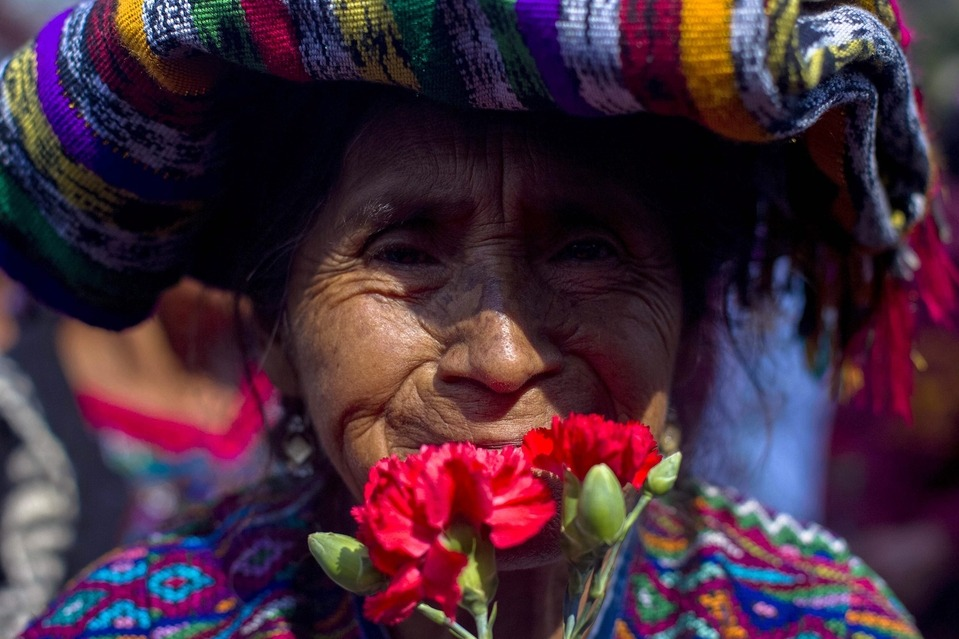 A woman carried flowers on Friday in Guatemala City after a judge Thursday suspended the genocide trial of former Guatemalan dictator Efrain Rios Montt, saying all actions taken since November 2011 are void in the case of the retired general charged with war crimes. Saul Martinez/European Pressphoto Agency
