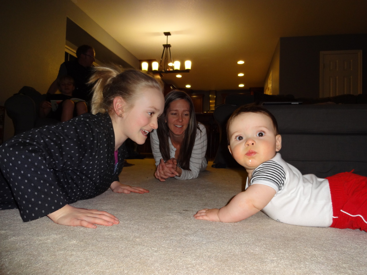 The trying to teach him how to crawl phase, assisted by his cousin. He's not interested in forward motion just yet, but appears to have the scoot backwards down to a tee.