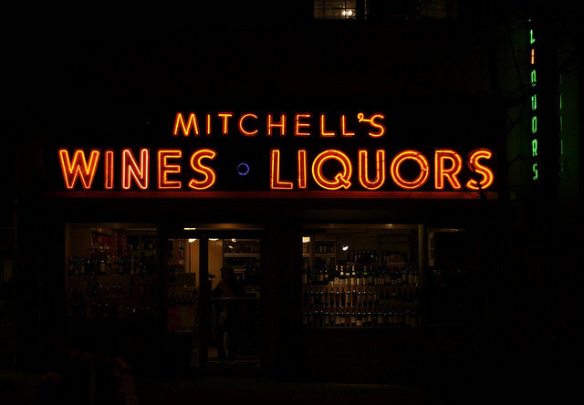 Mitchell's Wine & Liquor Storein the Upper West Side on W 86th St between Amsterdam & Broadway Recently I received a tip from Project Neon reader Rob B. who warned me that the neon sign at Mitchell's will be removed in a spring renovation. Noooo! I really like this sign. It's not the most elaborate sign in New York, but it dates from the '40s according to New York Neon, and I find it appealing. I like the dark blue circle between Wines and LIquors, I like the odd tail to the Q, and I like the addition of the green vertical sign to the right. It all adds up to a nice sign I'd be sad to see go.  I stopped by on Christmas eve to pick up a new bottle of Marsala, my secret ingredient in many stews and sauces (and a great pick-me-up for the chef as well). The shop is lovely, and though small, packed to the gills with bottles of every alcohol around. Rolling ladders allow the staff to reach the upper echelons of the wooden shelves, giving the shop a ship-like feel. The staff were friendly and seemed sympathetic to my inquiries about the sign, but alas my Spanish has rusted shut from years of disuse and the English of the gentleman I spoke to was a little tricky to make out. It sounds like the street level shops along the large building (200 W 86th Street) are all getting renovated, and with the renovation the liquor store is ditching the sign. That would be terrible! The sign looks to need some repair — there were a few letters out and one letter on the vertical sign was missing its tubing — but that's certainly no reason to scrap the whole thing. I'm going to do a little more investigation and see if I can find the name of the shop owner and maybe get more of the story. In the mean time, if you would like to write the shop and tell them how much you love the sign, their full address is: Mitchell's Wine & Liquor200 West 86th StreetNew York, NY  10024 I'll let you know any updates as I hear about them. Let's save this sign!