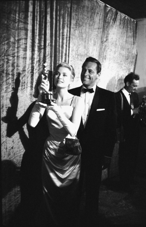Grace Kelly holds up the Oscar she won for her performance in The Country Girl as her co-star William Holden stands behind her, 1955.