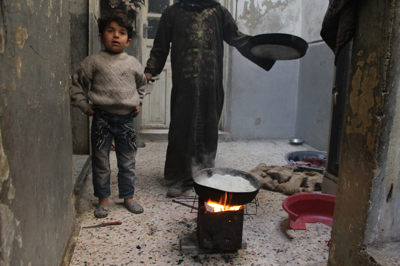 Aleppo - A mother cooks rice on a make-shift stove for her family. Solar power stoves would be an improvement for families inside Syria.