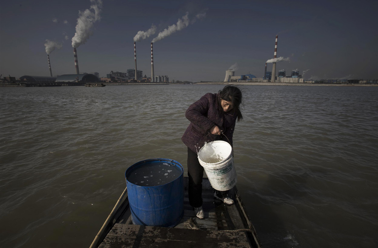 From China's Toxic Water, one of 17 photos. On World Water Day, a look at part of southern China. Here, a woman fetches water from the Yangtze river. Fifty families of fishermen live in Yanglingang village. They fish for their livelihood and have been drinking water from the Yangtze for decades. In the last few years, however, the river has been significantly polluted, and the fishermen noticed that the water has a strange flavor. Since 2003, factory construction has erupted all around Yanglingang. Today the little fishing village is surrounded by power plants, paper-making factories, and chemical plants. (© Lu Guang/Greenpeace)