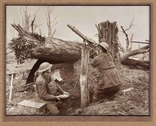 An Australian soldier of the 1st AIF scans the sky with his Lewis gun for enemy aircraft while his mate holds a pan magazine for a quick reload. The colour patch on the kneeling soldier appears to be of 8th Battalion, 2nd Brigade or possibly the 12th Battalion, 3rd Brigade. c.1917.