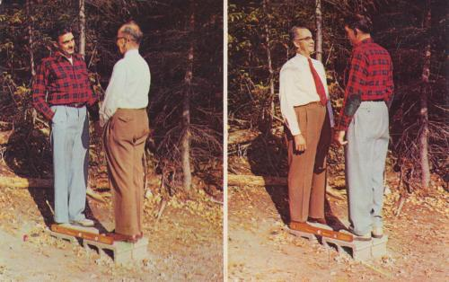 "THE MYSTERY SPOT - ST. IGNACE, MICHIGAN  In the early 1950's, three surveyors named Clarence, Fred and McCray came from California to explore the Upper Peninsula. They stumbled across an area of land where their surveying equipment didn't seem to work properly. For instance, no matter how many times they tried to level their tripod, through the use of a plum-bob or level, the plum-bob would always be drawn far to the east, even as the level was reading level. As they continued their research of this land, they noticed a constant feeling of being light-headed. Later, realizing their queasiness and problems with the surveying equipment only occurred in an area about 300 feet in diameter, they felt they had discovered a ""Mystery Spot"". Millions have visited their Mystery Spot and many return year after year to experience the unusual sensations that occur within its boundaries. Where else can a tall person seem smaller by comparison or a visitor climb a wall and tilt precariously into the air but not fall? The laws of gravity seem uneasy while sitting in a chair with its back legs balanced on a beam and front legs suspended in the air. You will without a doubt remember your visit to the Mystery Spot for years to come. —The Mystery Spot Website * * *  Jordan Smith is the guide to ephemeral America for The American Guide. He currently works for the University of Notre Dame during the day and scans at night. He lives in South Bend, Indiana and you can find him on Flickr, his blog, or one of several Tumblr sites."
