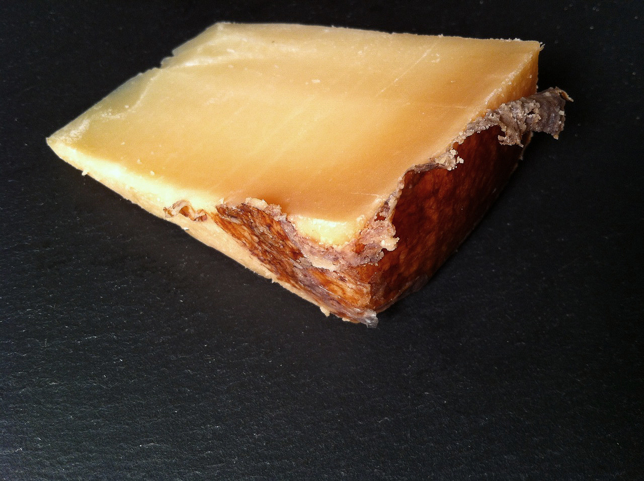 Il Pastore, from Latteria Sociale Santadi, is a brown-waxed sheep's milk cheese made in Santadi,a commune in Sardinia, Italy. The color of the wax evokes the old tradition, from the region, of packing a layer of clay and mud onto the wheels of cheese to protect them, in the days before wax was in ready supply. Made with raw sheep's milk cheese and aged for at least 3 months, this pecorino is similar to Manchego and is an excellent substitute for the Spanish classic. The brown, mottled rind peels back to reveal a firm, golden paste turning to light-caramel brown near the rind. The paste is dry, dense, a bit crumbly, with a light oily sheen. The flavor is salty, nutty and complex, with lanolin, gamey and smokey notes and just a bit of peppery bite. On a whim, I used the Il Pastore in a 3-green Tart recipe ( spinach, chard and kale), mixed with Bulgarian Feta, which worked out beautifully, the Feta, with it's fresh lipase bite, complimenting the aged Il Pastore nicely. Purchased at Stinky Brooklyn.