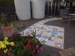 COMMUNITY MADE ART IN PUBLIC PLACESSydney Eastern Suburbs community artist, Karen Weiss, worked with children to create these squares of mosaic tiles which were later installed by people from the community wanting a new experience and and who worked with a landscape construction expert.The purpose of the project, supported by Randwick City Council in Sydney, was to bring colour to the drab paving of a public barbecue area in the Permaculture Interpretive Garden on Munda Street, Randwick.Rather than make judgements on the artistic aspects of he work based on conventional art criticism standards, this work, which makes no claims to greatness, is best judged on criteria of community participation and engagement. In this, it can only be called a success.