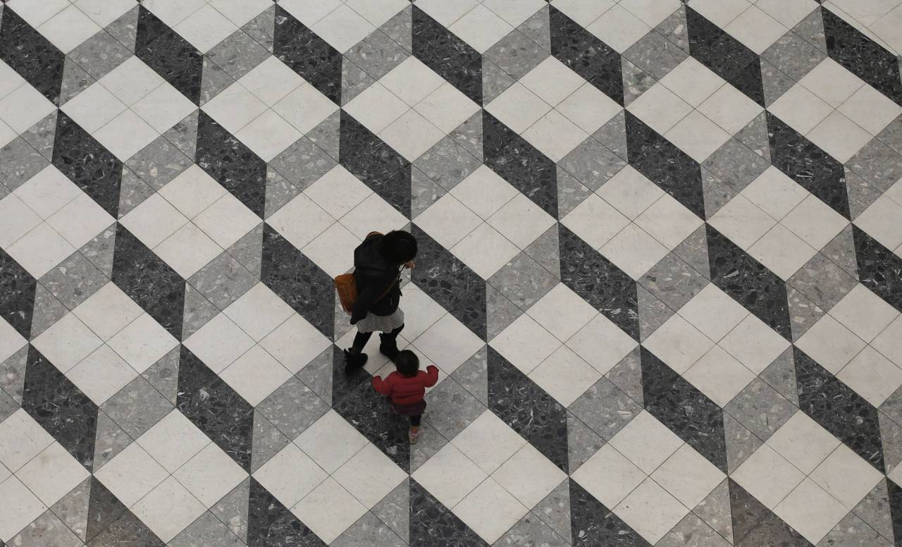 Optical illusion. A girl and her mother walk in a building in Tokyo. Square making an optical illusion with his geometric draw. Illusion d'optique. Une petite fille marche avec sa mère au pied d'un building de Tokyo. Les formes géométriques dessinés sur le parvis de ce bâtiment forment une illusion d'optique. PHOTOGRAPHER : REUTERS/TORU HANAI