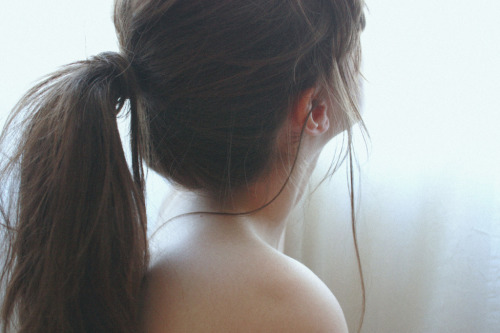 littlings:  (by nathalie paige) The Girl with the Ponytail  When I was younger, although perhaps not that much younger, I saw the girl with the ponytail as the girl who could conquer all. She was old enough not to need her mother to plait her hair anymore, but still so young that she had not yet developed any real sense of organization, limiting her mornings to quick breakfast, choice of outfit, teethbrushing, and left no time to think about her hair as she dashed out the door. So she secured her locks with a thin, sparkly hair elastic that she kept permanently wrapped around her wrist when she was not using it, and with this hairdo she would go out and do whatever people that age would do at that time. The girl with the ponytail was for me the epitome of early adolescence: her newly-pierced ears were visible and she would show off her smile, and she could easily pull her hair back if it got in the way as she was bending over her algebra homework, or while playing volleyball, or when she kissed her first boy. Whenever I was in a drugstore with my mom the first thing I would do was run to the beauty aisle and take in all of the hair accessories put on display, hoping that by touching each elastic, clip or bobby pin long enough, I would be one step closer to being transported into the realm of the older girls I so admired. The years went by, and the girl with the ponytail met a man who convinced her that her long hair was beautiful, and so she ceded her spot to me, thus continuing the cycle. But I never kept my hair in a ponytail when the time was right, but rather in a bun, as was fashionable at the moment, for fear of being ridiculed, and I never did my algebra or picked up a volleyball or kissed my first boy like my ponytailed idol had. And now I wonder at what I did wrong not to have the childhood I'd wished for, and now I wish I could meet myself as a little girl, all wide-eyed and innocent, and tell her not to expect anything from anybody: things will never go according to plan.