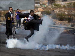 diaspora:  A Palestinian lawyer wearing his official robes kicks a tear gas canister back toward Israeli soldiers during a demonstration by scores of Palestinian lawyers called for by the Palestinian Bar Association in solidarity with protesters at the Al-Aqsa mosque compound in Jerusalem's Old City, near Ramallah, West Bank