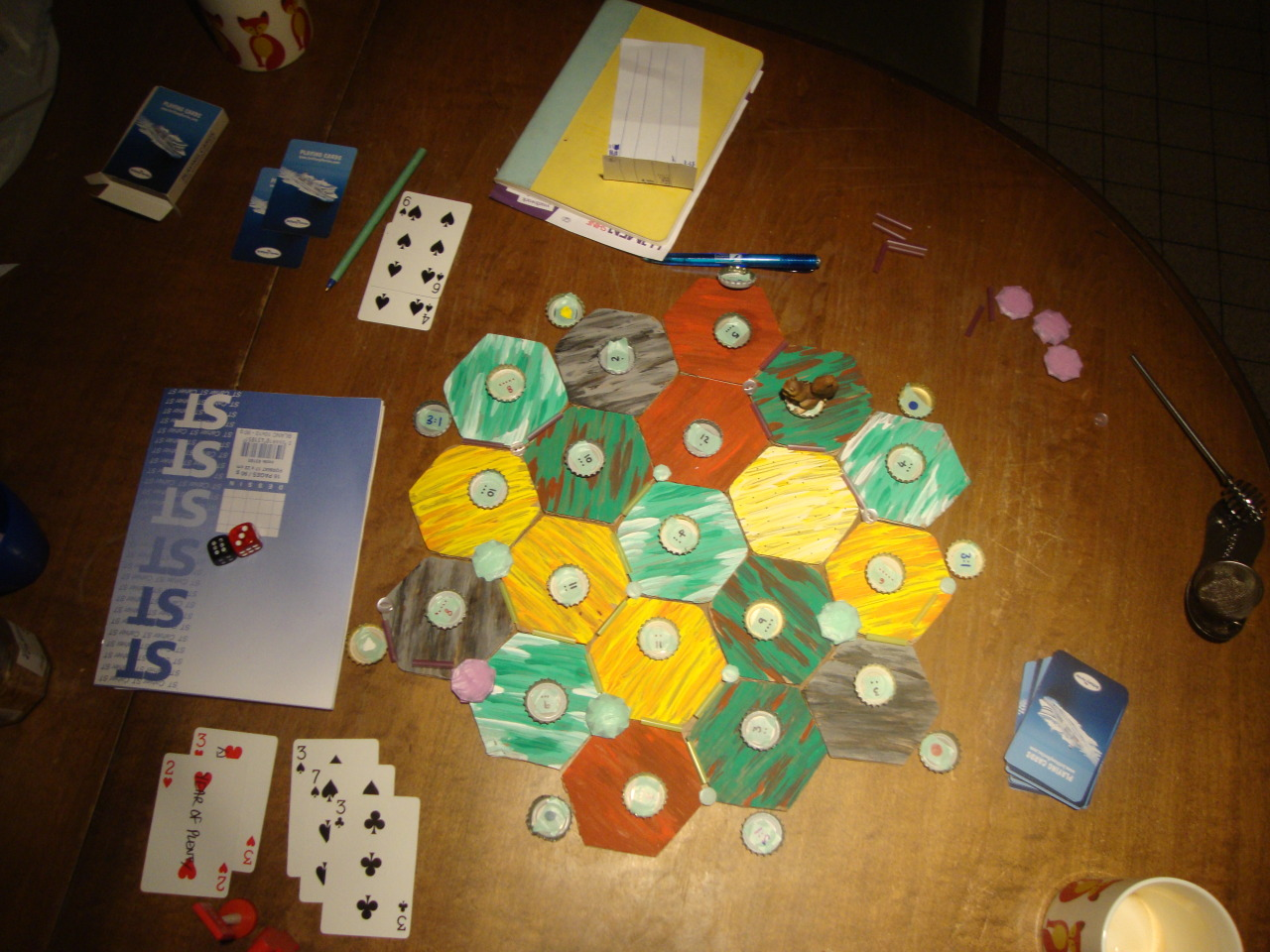 homemade two player Settlers of Catan all you need: 19 painted cardboard hexes 27 numbered beer bottle caps  2 dice 8 big buttons (cities) 10 small buttons (settlements) straws, cut into 1 inch lengths (roads) small toy squirrel (the robber) old deck of cards and a sharpie (development cards) pen and paper (recording resources tally style)