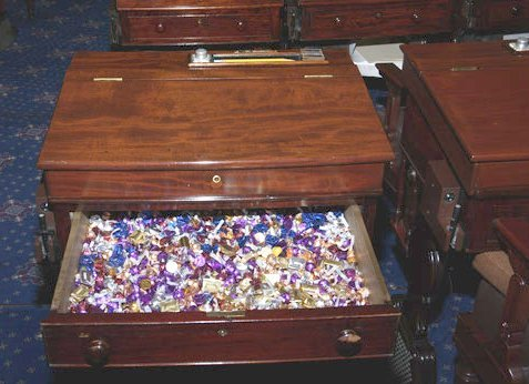 "In 1965, California senator George Murphy began keeping sweets in his desk on the Senate floor, and he offered them to colleagues who passed by. Because Murphy sat near a busy entrance, the ""candy desk"" became well known, and when Murphy left the Senate after one term the tradition was maintained. In the ensuing years Slade Gorton, John McCain, George Voinovich, and Rick Santorum have all sat at the candy desk, each stocking it with confections from his home state. (In Santorum's case, this was a bonanza — Hershey shipped more than 400 pounds of chocolate each year from its Pennsylvania headquarters.)"