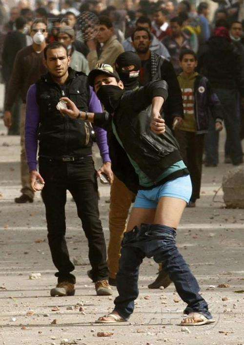 With his trousers down to show defiance, an Egyptian protester throws stones at riot policemen and other demonstrators who took the side of security forces during clashes near Cairo's Tahrir Square at the weekend. AFP PHOTO/MOHAMMED ABED