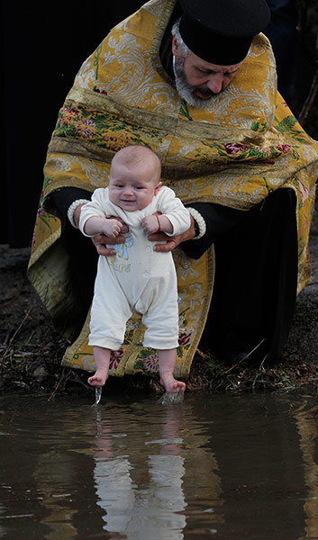 Epiphany celebrations - An Orthodox priest baptises a baby in the icy waters of the river Tundzha during celebrations of Epiphany in the town of Kalofer, Bulgaria Photograph: Valentina Petrova/AP