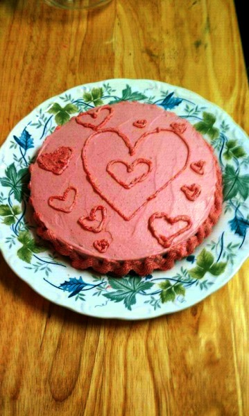 "Lemon-Ginger Cake with Raspberry Buttercream Frosting I made this cake for a friend's birthday and it was so good I had to make it again as the perfect Valentine's Day cake! It now holds a place in my favorite cake repertoire (even though it's not chocolate!) The cake recipe is basically the same as the Lemony French Cake at the lovely vegan blog havecakewilltravel.com just doctored up a bit and my recipe for raspberry buttercream. Enjoy! Lemon-Ginger Cake: 1 cup soy yogurt (preferably lemon or vanilla) 1 cup powdered sugar (sifted) 1/2 cup veg. oil 1 teaspoon vanilla zest and juice of 1 lemon 1/2 teaspoon fresh ginger (grated) 1 1/2 cup flour 2 teaspoons baking powder pinch of cardamom Preheat oven to 350 degrees. Grease two 6"" across by 2"" deep pans. Mix ingredients #1-6. Sift in rest of ingredients and stir until just combined. Pour into pans and bake until outsides are golden and toothpick comes out of center clean, about 20-30 minutes (depending on pan size and material.) Raspberry Buttercream Frosting 1 c raspberries 1/2 teaspoon balsamic vinegar 3/4 cup earth balance butter 2 cup powdered sugar (sifted) 1 teaspoon vanilla First puree your raspberries in a food processor. Next pour pureed raspberries into a small pot and add balsamic vinegar (it sounds strange but it really helps bring out the raspberry flavor!) Heat just until boiling. Let raspberries cool and then pour through a sieve our cheesecloth, straining out all the seeds so you only have a thick juice, set aside. Cream butter until light and fluffy. Slowly add sifted sugar. Add vanilla. VERY slowly add raspberry juice one teaspoon at a time, mixing to incorporate after each addition. You may not need all of the juice, and be careful to watch that the frosting is not starting to separate- STOP adding juice if you see any signs of separation. It should be a lovely bright pink with a nice sweet/tart flavor."